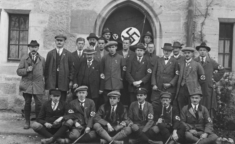"""NSDAP-Delegation im Oktober 1922 auf dem """"Deutschen Tag"""" in Coburg, einer Großveranstaltung des Deutschvölkischen Schutz- und Trutzbundes, darunter Oskar Körner (li. stehend mit Pfeife und Hut) und Oluf Christensen (re. stehend)."""